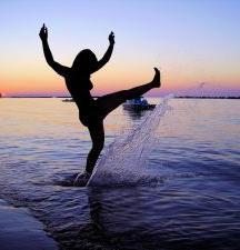 silhouette of girl splashing water at sunset