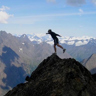 Man balancing on top of mountain peak