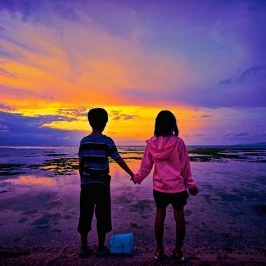 two children holding hands in the sunset