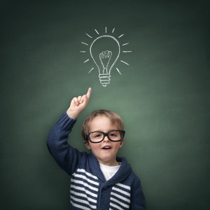 Schoolboy standing in front of a blackboard with a bright idea l