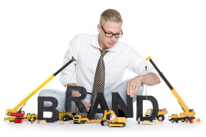 Build up a brand concept: Smiling businessman building the word