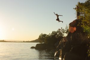 Man leaping off cliff into water